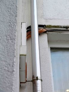Offene Kabelschacht, außen an der Hauswand.